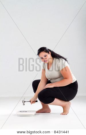 woman hitting scale with hammer