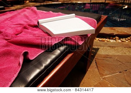 Book on a chaise lounge.
