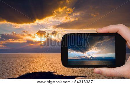 Tourist Taking Photo Of Sundown On Dead Sea