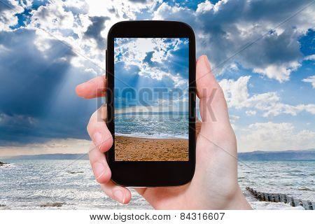 Tourist Taking Photo Of Sunbeams Over Dead Sea