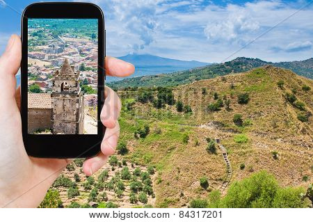 Tourist Taking Photo Of Town On Etna Slope