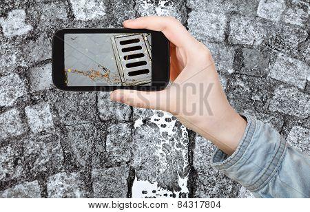 Tourist Taking Photo Of Wet Cobblestone Road