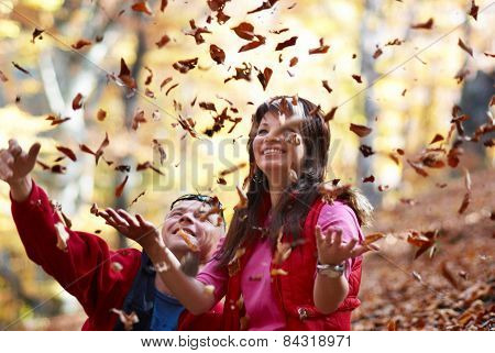 Young Couple Enjoying The Falling Leaves
