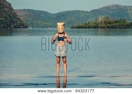 Woman With Paper Bag Over Head On Tropical Beach