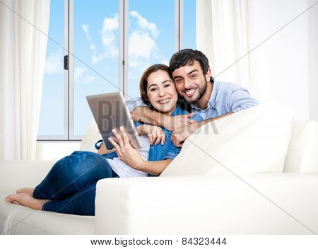 Young Happy Couple On Couch At Home Enjoying Using Digital Tablet