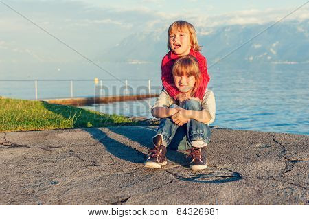 Two kids, little girl and boy resting by the lake on sunset