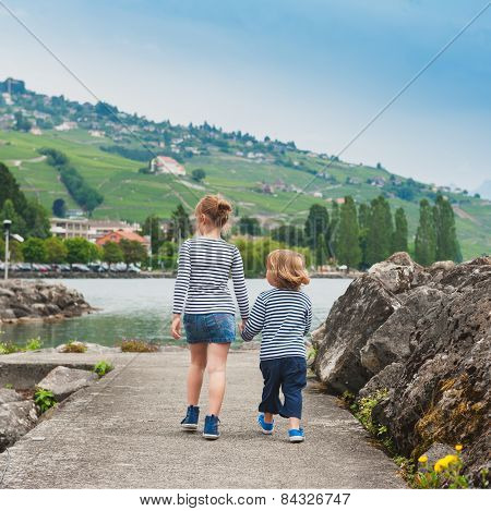 Two kids, brother and sister walking by the lake