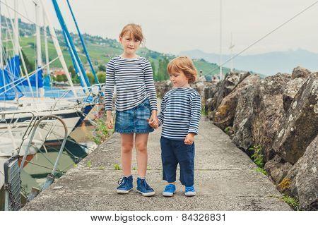 Two fashion kids, little girl and boy wearing frocks