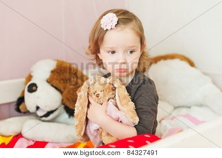 Interior portrait of a cute sad toddler girl in her room