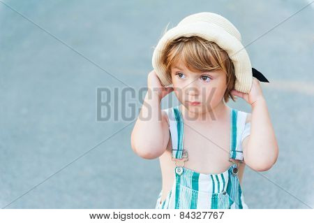 Summer portrait of adorable toddler boy, wearing overalls and hat
