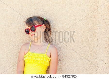 Portrait of a cute little girl wearing red sunglasses and yellow swimming suit