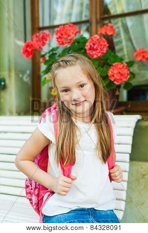 Outdoor portrait of a cute little girl resting on a bench after school