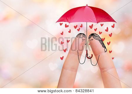 Conceptual finger art. Lovers are kissing and holding umbrella with falling flowers. Stock Image
