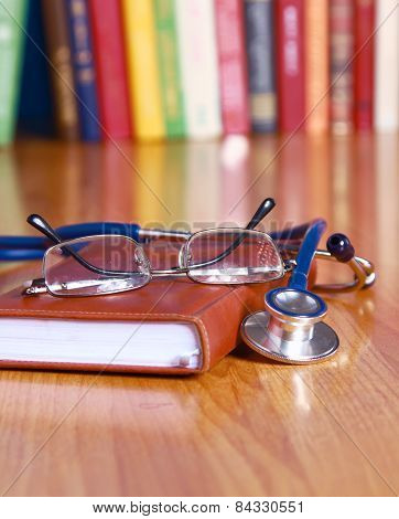 Stethoscope on book with leather cover and glasses