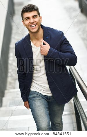 Young Man With Blue Eyes Smiling In Urban Background