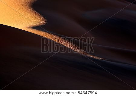 A slither of light drapes down a dune