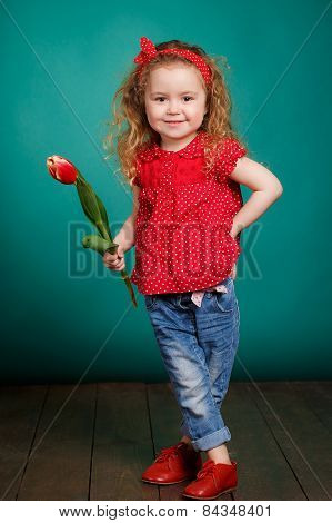 Beautiful little girl with red tulips.