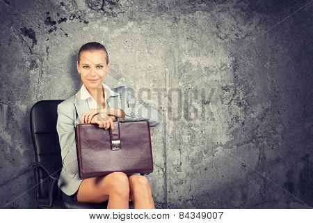 Woman wearing jacket, blouse holding briefcase. Background concrete wall