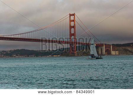 Sail Boat Passing Under The Famous Golden Gate Bridge