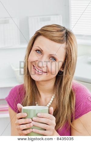 Portrait Of A Captivating Woman Holding A Cup Smiling At The Camera