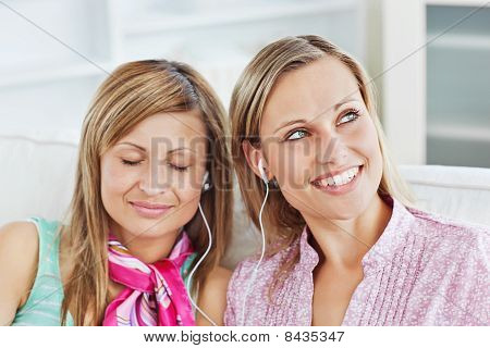 Relaxed Two Female Friends Listen To Music Sitting On A Sofa