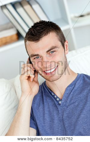 Happy Young Man Talking On Phone Smiling At The Camera