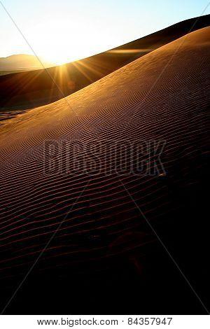 Starburst Sun rising over the sand dunes of Sossusvlei, Namibia.
