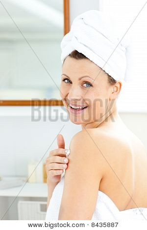 Delighted Young Woman Putting Cream On Her Body Looking At The Camera
