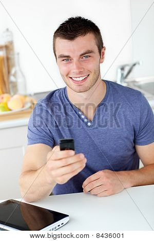 Lively Young Man Sending A Text Smiling At The Camera