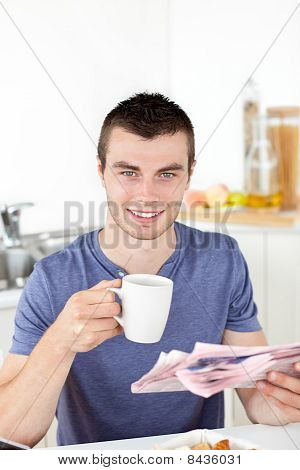 Positive Young Man Holding A Cup And A Newspaper Smiling At The Camera