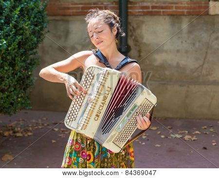 Female Street Musician Is Playing The Accordion