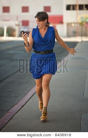 Excited Woman Walks And Calls On Cell Phone.