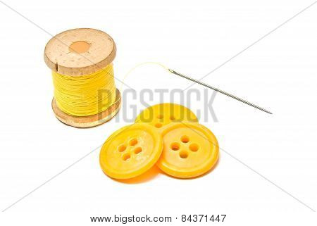 Buttons And Spool Of Yellow Thread On White