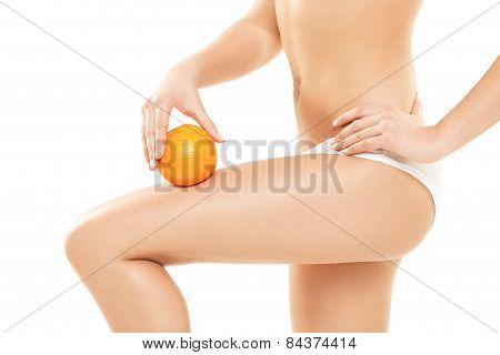 Young Woman In Underwear Holding An Orange Showing Absence Of Cellulite Over White Background