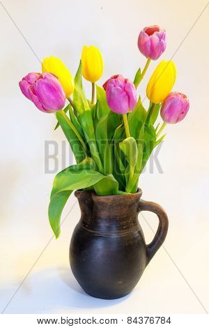 Bouquet Of Pink And Yellow Tulips In An Old Clay Pot, Isolated On A White Background