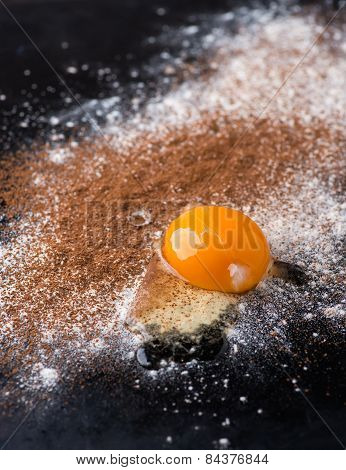 Dusted Wheat Flour, Cocoa Powder And Egg On Dark Background