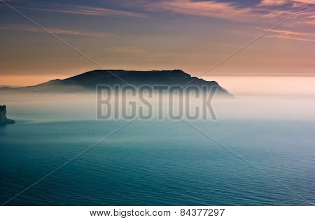 colorful sunrise with haze above cape in Black Sea