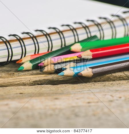 Checked blank notebook with multicolored pencils on wood background
