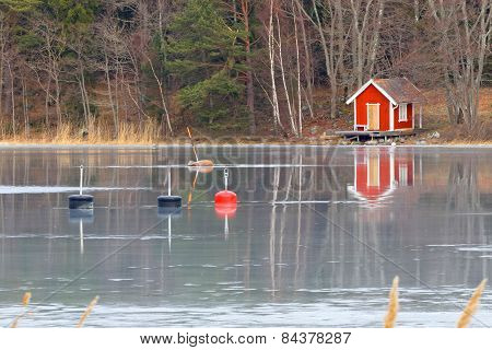 Red Boat House Reflecting In The Ice