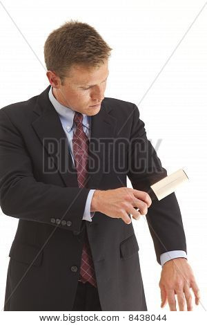Young businessman using lint brush