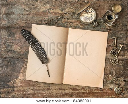 Open Book And Vintage Writing Accessories. Textured Wooden Background