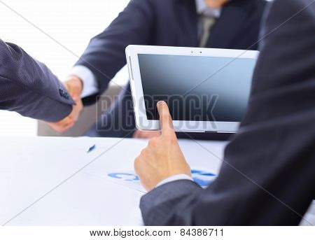 man with finger touching screen of a digital tablet