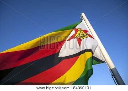 The zimbabwean flag flying in the afternoon light