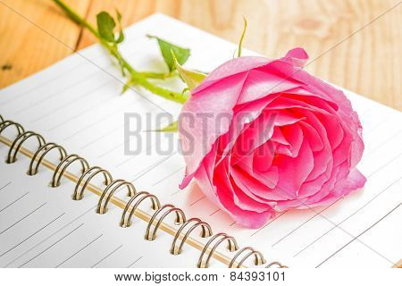 Pink Rose And Diary On Wooden Table.