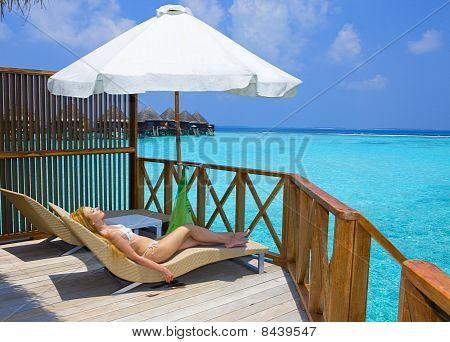 Joven bonita a mujer en plataforma en villa agua Maldivas