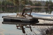 image of dock a lake  - Two wood slatted outdoor chairs on a dock at the edge of a lake - JPG