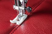pic of sewing  - sewing machine and red leather with a seam close - JPG