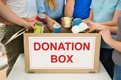 stock photo of tin man  - Group Of People Putting Cans In Donation Box - JPG