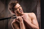 pic of choke  - Frustrated young man choking by his necktie while standing against metal background - JPG