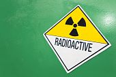 stock photo of radioactive  - A radioactive warning sign on a green container of radioactive material - JPG